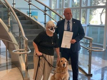 Fresno Mayor Jerry Dyer presents resident Toni Eames and her guide dog Adora with the Proclamation for International Assistance Dog Week.